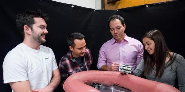 Mechanical engineering Associate Professor Mark Rentschler (far right) with graduate students (left to right) Levi Pearson, Greg Formosa and Micah Prendergast with an oversized version of a synthetic colon created as a senior design project.