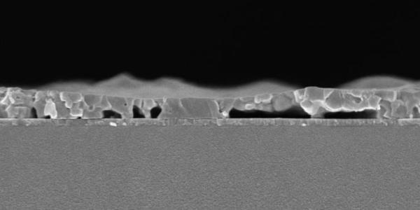 Cross-sectional SEM image of the spin-coated MAPbI3 film processed from DMF precursor solution (annealed for 5 s at 100 °C) on a PTAA-covered ITO glass substrate.