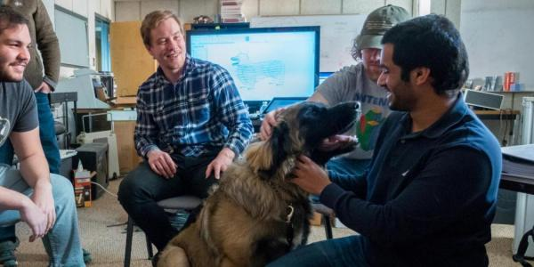 The team interacts with a real dog as part of their research.