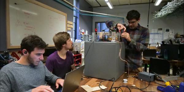 Joss Gitlin, Andrew Shepherd and Julian Torres troubleshoot their safecracking robot in the BTU Lab