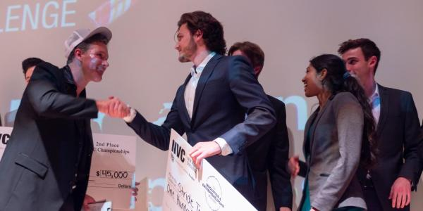 Tim Visos-Ely holds a giant check after winning the New Venture Challenge