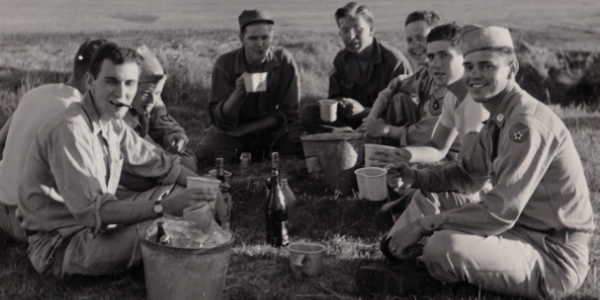 Eight air force students enjoy a picnic in a grassy field