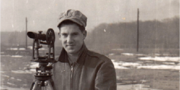 Black and white photo of student posing with a transit (surveying device)