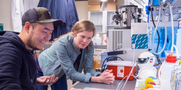 A graduate student and his advisor discuss a project in their lab