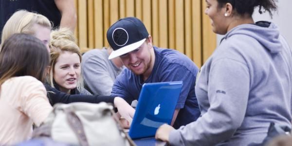 Students discuss classwork around a laptop in a lecture hall
