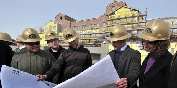 A group of construction engineers looks at blueprints outside a campus building under construction