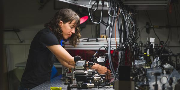 A graduate student works on an electrical engineering project in her lab.