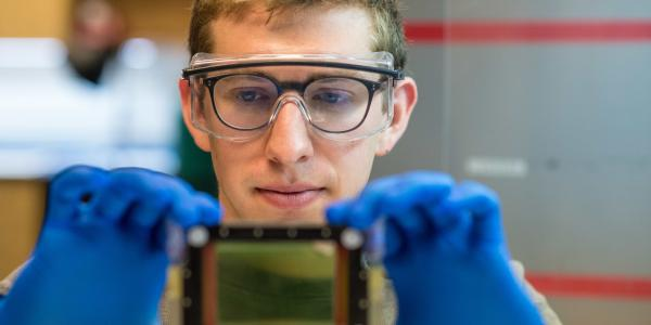 student in safety glasses holding a device towards the camera