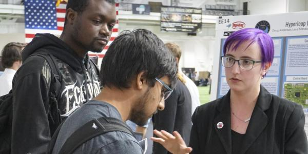 Woman with purple hair describes senior capstone project at engineering projects expo
