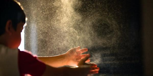 A boy clapping hands to show water spray into the air