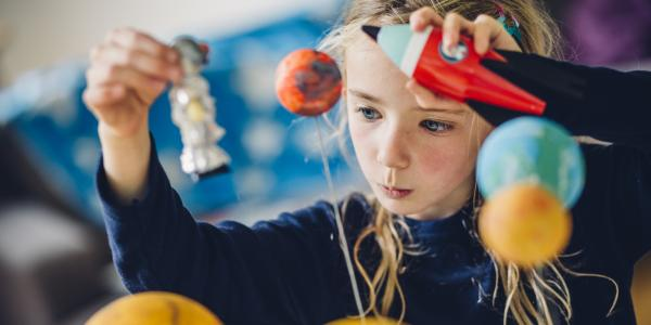 girl playing with solar system