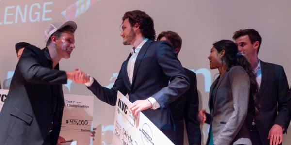 New Venture Challenge teams hold large checks on stage