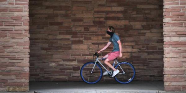A student rides his bike near the UMC