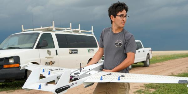 student with drone in field