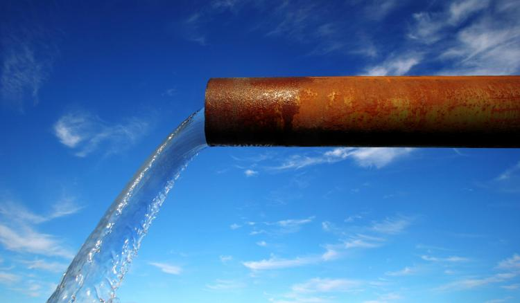 Rusty pipe pouring out water
