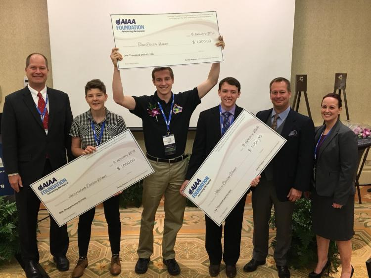 Students from the winning teams with oversized prize checks.