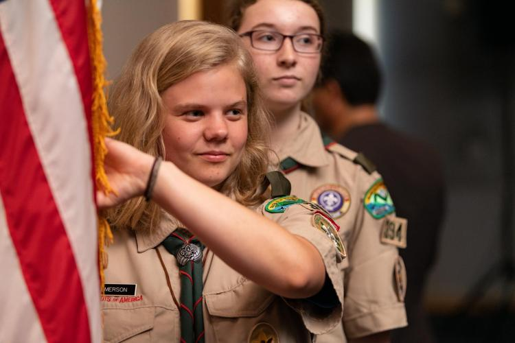 Emerson Domke in scout uniform holding flag