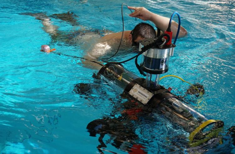 Student in the pool with the RoboSub system