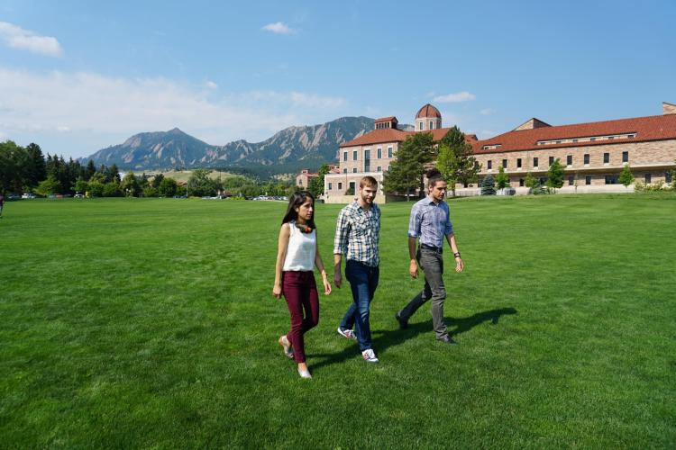Graduate students walk across field on campus