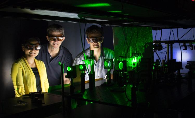 Rafael Piestun and his students standing in a lab with a laser