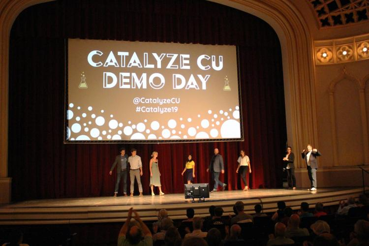 Catalyze participants walk on stage at Demo Day