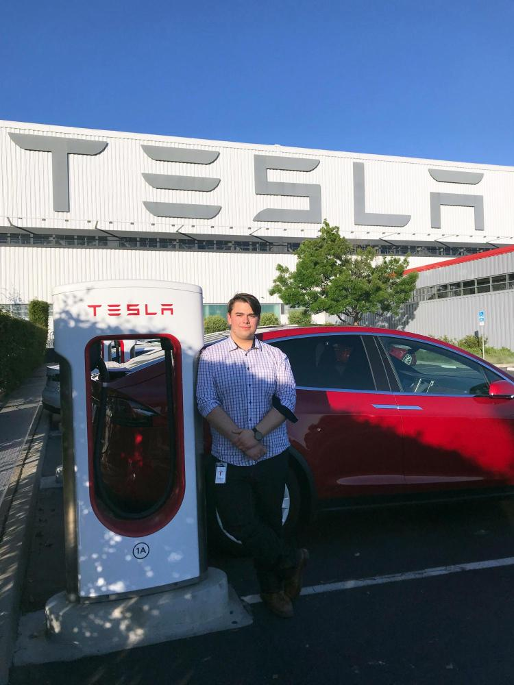Cam Humphreys stands outside Tesla factory in California.