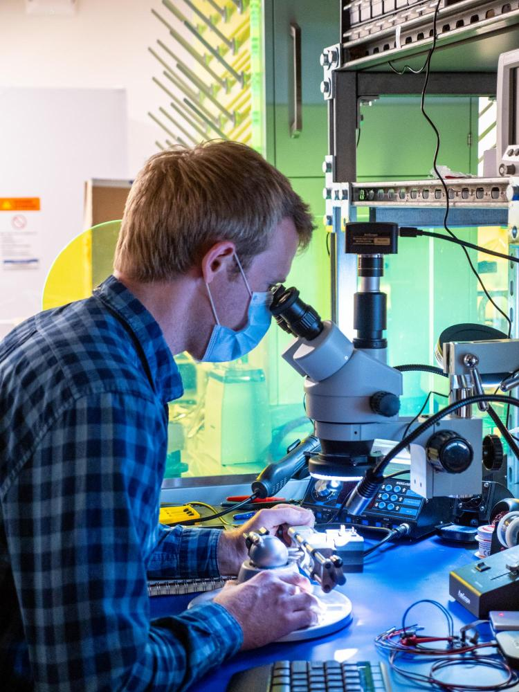 Graduate student at microscope in robotics lab