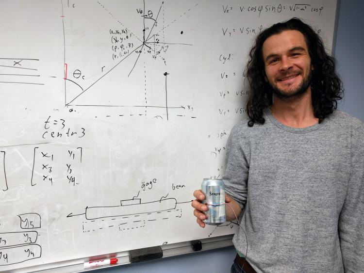 Keith Regner in front of whiteboard with strain gauage.