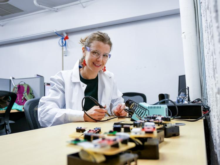 Architectural engineering PhD student Margarite Jacoby working on a board controller.