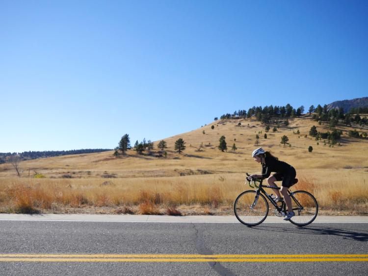 A woman rides her bike along a Boulder backroad.