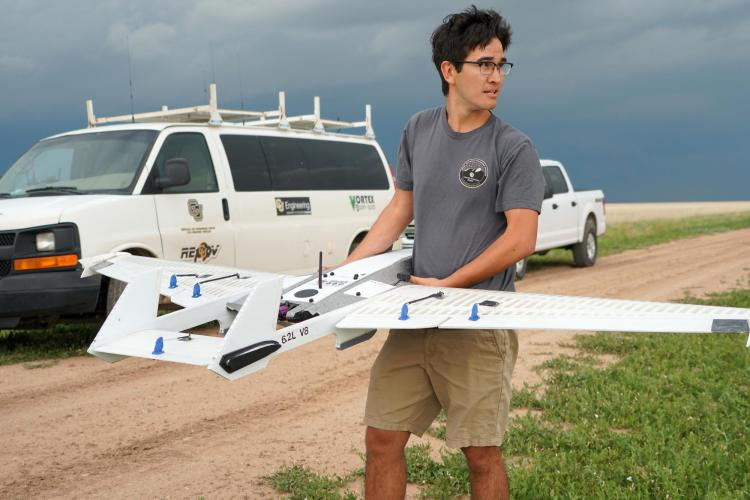 A student standing with the drone in a field before deployment