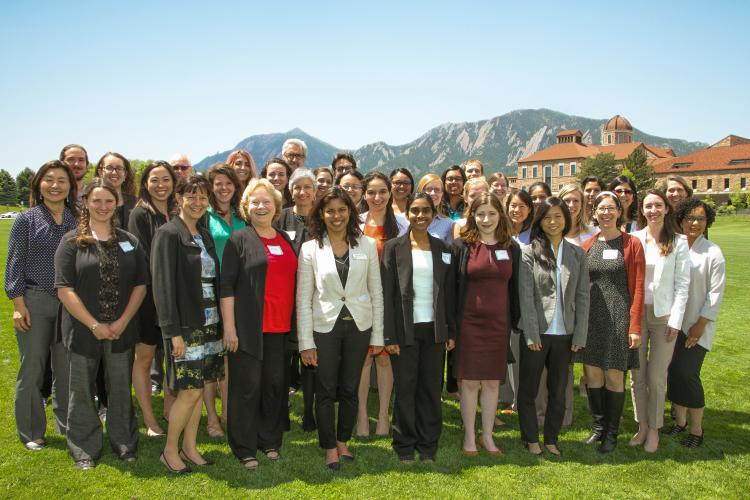 The Women in Aerospace Symposium standing for a group photo outside with the Flatirons in the background.
