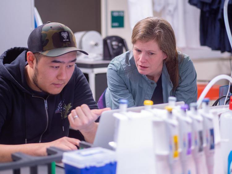 Lynch working in the lab with a student
