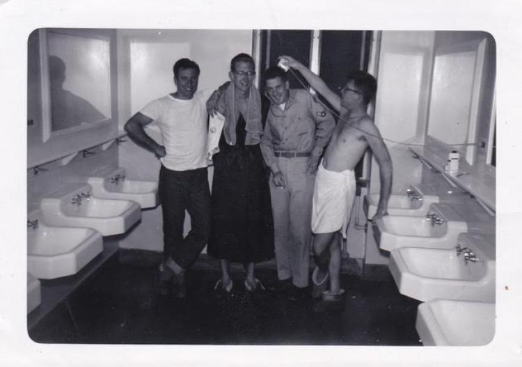 Four male students posing for a photo in their dorm bathroom