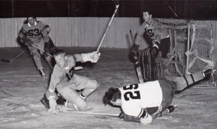 Four students playing hockey and sliding on the ice