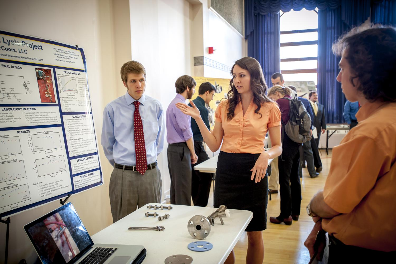 A student explains her project to a guest at the mechanical engineering expo.