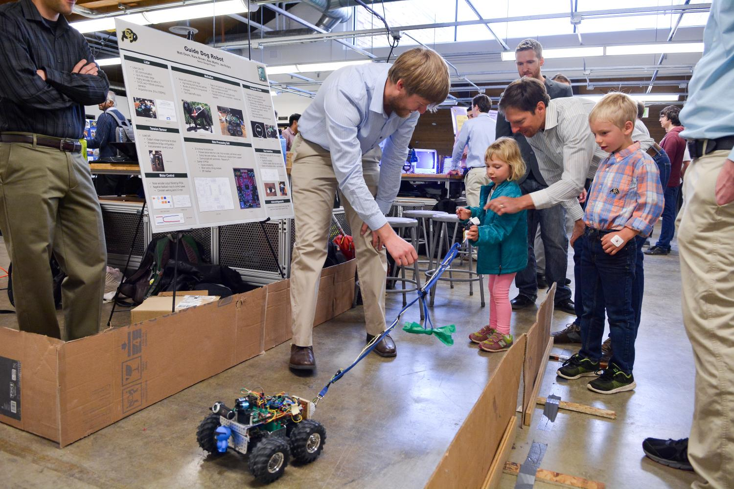 A child operates a guide dog robot at the 2016 ECEE senior design expo.