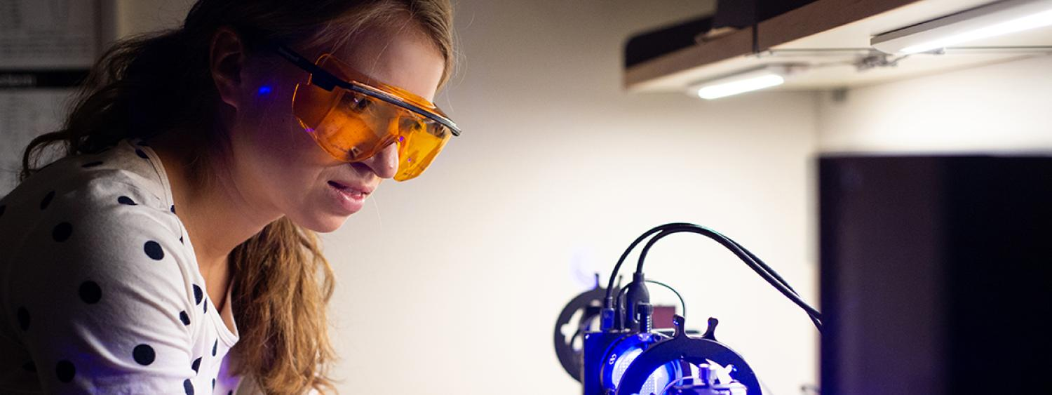 A student working with a laser in the lab
