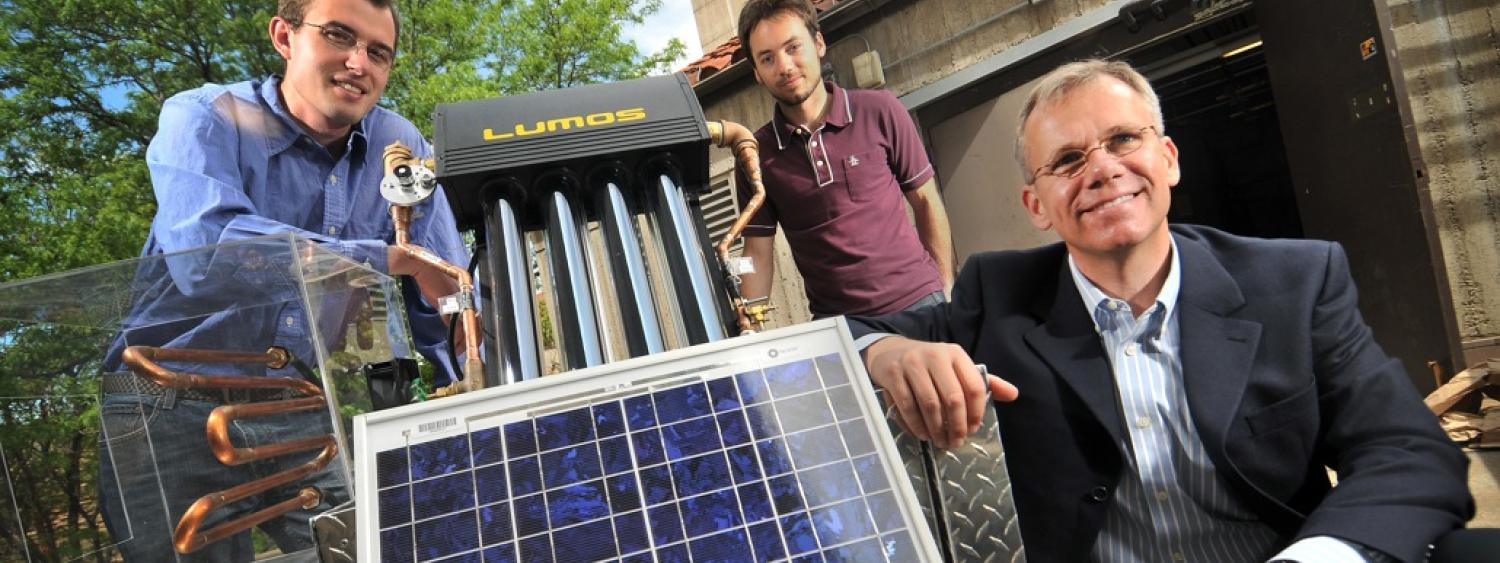 Professor and students looking at solar panel