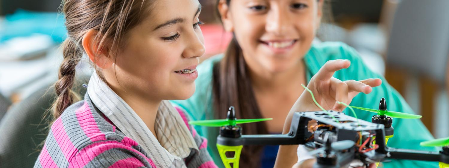 CU Engineering provides education programs and partners with K-12 teachers. Pictured here are two middle school young girls engaging with an unmanned aerial vehicle.