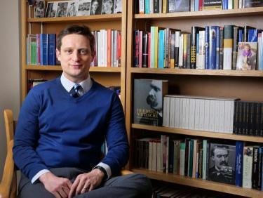Professor Shilo Brooks near bookcase