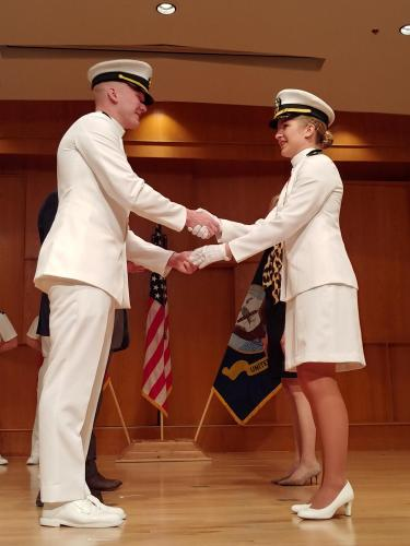 Ensign Gemma Novak renders her first handshake and challenge coin exchange as a new Navy officer.