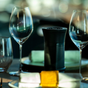An air purifier the size of a water bottle sits among wine glasses on a restaurant table