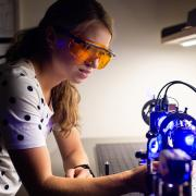 A student working in the lab with lasers