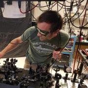 Brendan Heffernan adjusts optical components at a light table in the team's lab.