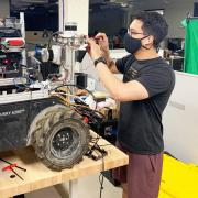 Dan Torres wears a mask while working on one of the DARPA Subterranean Challenge robots