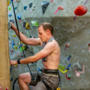 Andrew Dahir climbs on the climbing wall during his record attempt