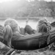 A black-and-white photo of two girls sitting next to one another, on a hammock, faces away from the viewer