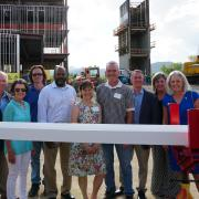 A group of officials standing with the final beam.