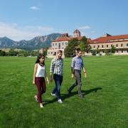 Graduate students walk across field on campus